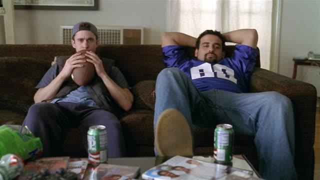 Medium shot two men sitting on sofa watching TV / one of the men talking to someone offscreen