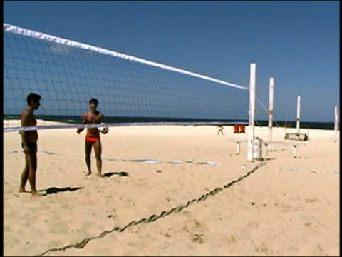 medium shot two men smiling and gesturing at cam / wide shot pan zoom in zoom out four men heading + kicking volleyball on beach - menschliche gliedmaßen stock-videos und b-roll-filmmaterial