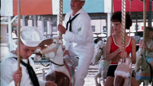 1965 medium shot two sailors flirting with young woman on carousel - sailor suit stock videos and b-roll footage
