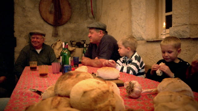 vidéos et rushes de medium shot two senior men and two young boys sitting at table eating bread / provence, france - voix