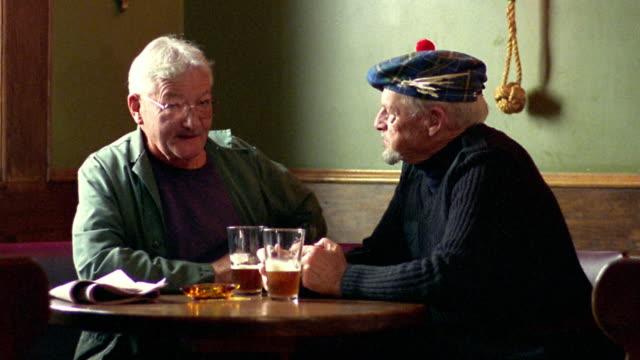 stockvideo's en b-roll-footage met medium shot two senior men sitting in pub talking and drinking beer / one in tam-o'-shanter / nova scotia - 70 79 jaar