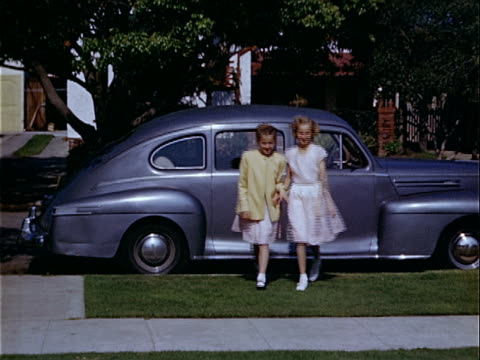 1949 medium shot two sisters walking side by side up sidewalk near lincoln zephyr / los angeles, california, usa  - 1949 bildbanksvideor och videomaterial från bakom kulisserna