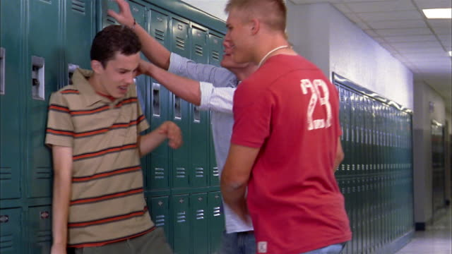 Medium shot two teenage boys hanging boy on locker by shirt