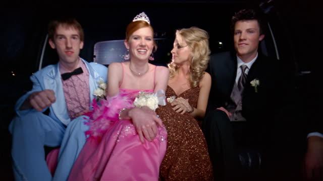 medium shot two teenage couples in formalwear riding to prom in limo - coppia di adolescenti video stock e b–roll
