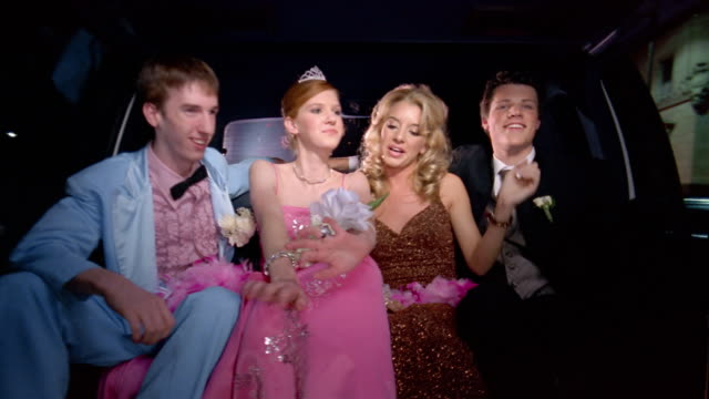 medium shot two teenage couples in formalwear riding to prom in limo / girls singing / geeky boy diving across friends laps - coppia di adolescenti video stock e b–roll