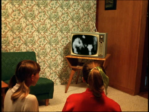 vídeos de stock, filmes e b-roll de reenactment medium shot two teenage girls sitting on floor and watching dance tv show in living room - 1950