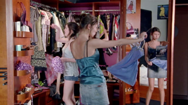 vídeos de stock, filmes e b-roll de medium shot two teenage girls standing in closet of bedroom, trying on dresses/ third girl walking in and looking at clothes - armário
