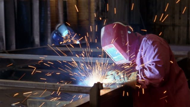 Medium shot two welders wearing masks and working in factory