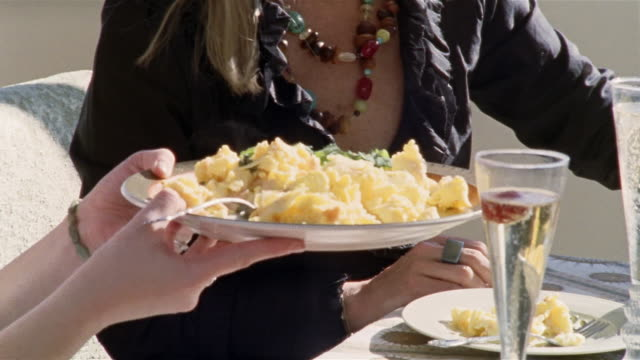 medium shot two women passing plate of eggs at brunch/ san francisco, california - brunch stock videos & royalty-free footage