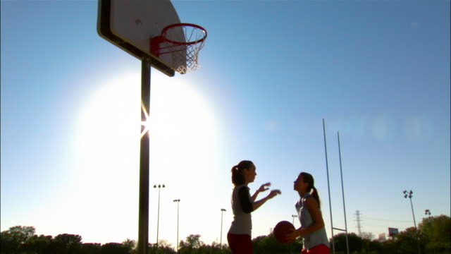 medium shot two women playing basketball/ dallas, texas - two people stock videos & royalty-free footage