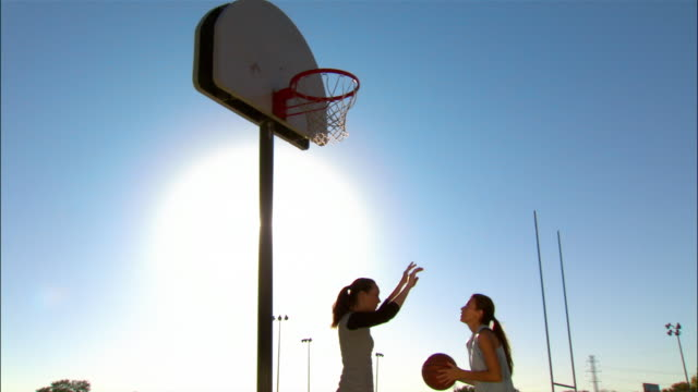 Medium shot two women playing basketball/ Dallas, Texas