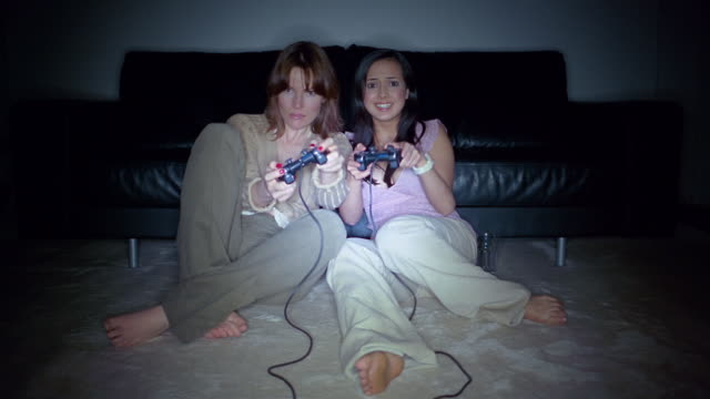 medium shot two women sitting on floor in front of couch playing video game / england - spielsteuerung stock-videos und b-roll-filmmaterial