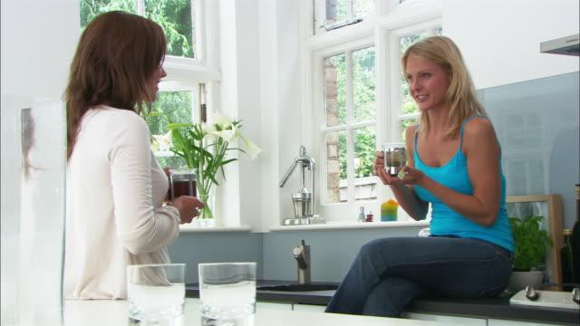 vídeos y material grabado en eventos de stock de medium shot two women talking and drinking tea in modern kitchen/ london - sólo mujeres jóvenes