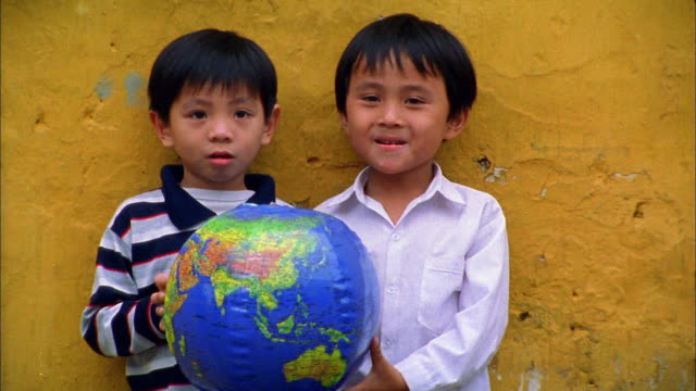 medium shot two young asian boys holding inflatable globe and laughing / hoi an, vietnam - children only stock videos & royalty-free footage