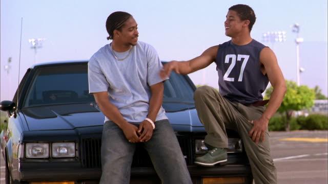 vidéos et rushes de medium shot two young black men sitting on hood of car and talking - capot de voiture