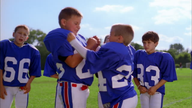 Medium shot two young boys wearing football uniforms hitting each other on shoulder pads/ boy falling down
