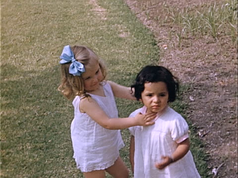 1939 medium shot two young girls hugging and wearing white dresses in park / los angeles, california, usa  - weißes kleid stock-videos und b-roll-filmmaterial
