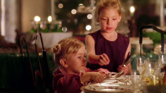 Medium shot two young girls setting dinner table