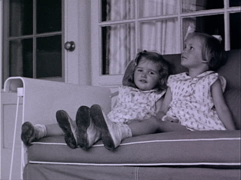 1939 medium shot two young girls sitting side by side on sofa on patio / los angeles, california, usa  - home movie stock videos & royalty-free footage