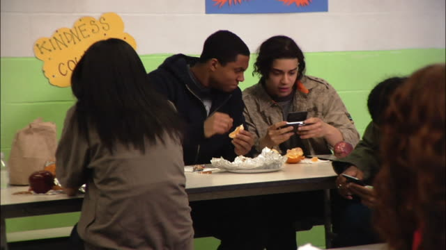 Medium shot Two young men giving each other street handshakes and using electronic organizer in cafeteria while eating lunch / New York City, New York, USA