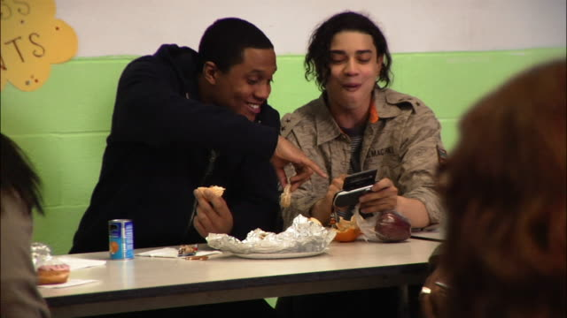 Medium shot Two young men having lunch and using electronic organizer in cafeteria / New York City, New York, USA