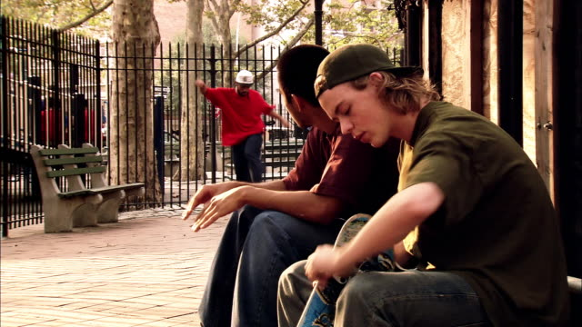 medium shot two young men sitting in park / fixing skateboard / man skateboarding in background / new york city - 18 19 years stock videos & royalty-free footage