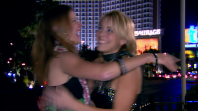 medium shot two young women hugging outside casino in city at night/ las vegas, nevada, usa - strapless stock videos & royalty-free footage