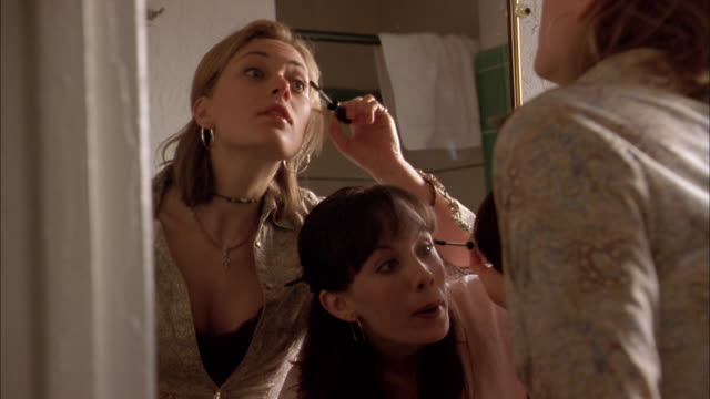 vidéos et rushes de medium shot two young women looking in mirror and putting on eyeliner - mascara