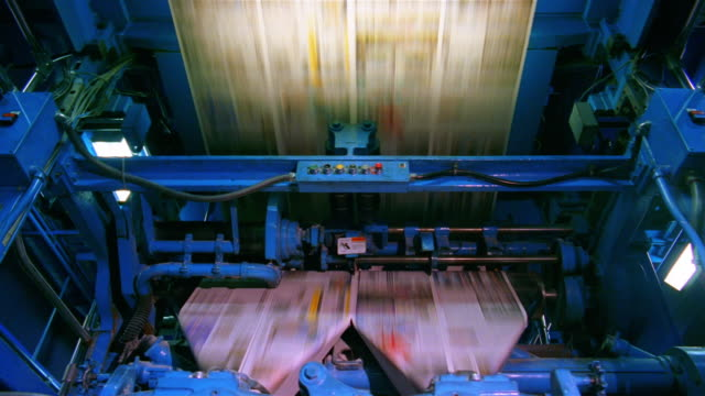 stockvideo's en b-roll-footage met medium shot uncut newspapers moving through printing press at santa barbara news press / santa barbara, california - drukpers