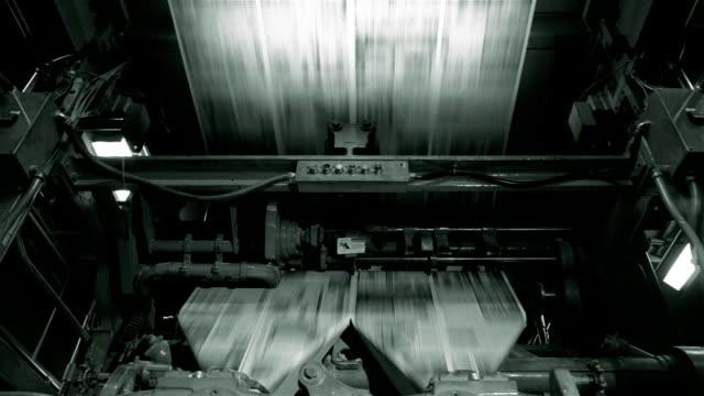 medium shot uncut newspapers moving through printing press at santa barbara news press / santa barbara, california - ジャーナリズム点の映像素材/bロール