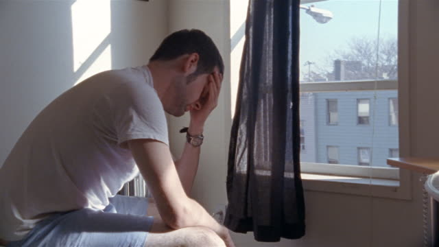 vidéos et rushes de medium shot unshaven man sitting on bed by window and rubbing face - tristesse