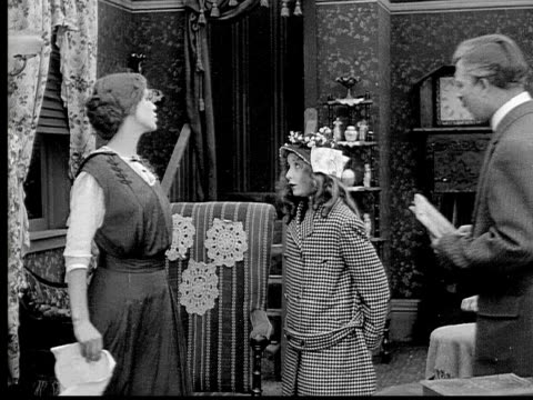 1913 b/w medium shot upset girl talking to her mother and father in living room before breaking down in tears / usa  - 1913 stock videos & royalty-free footage