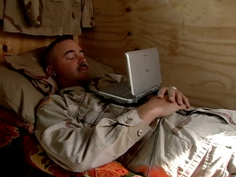 medium shot us marine lying on bed watching portable dvd player - dvd stock videos & royalty-free footage