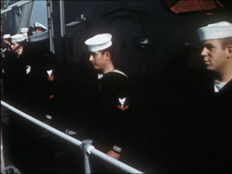 vidéos et rushes de medium shot us navy sailors on deck of ship saluting while rocking back and forth with ocean waves - bercement