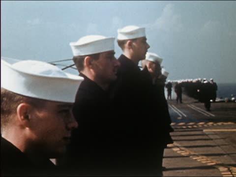 vidéos et rushes de 1962 medium shot us navy sailors standing at attention on deck / wind blowing cap off sailor in foreground - marinière