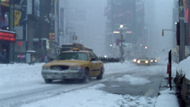 2003 medium shot vehicles driving through Times Square during blizzard / New York City