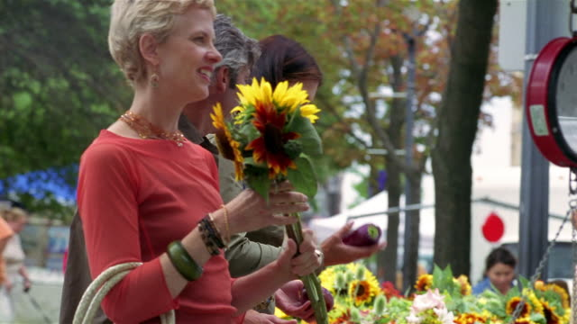 medium shot vendor selling sunflowers to woman at farmer's market / couple shopping in background / milwaukee - geben stock-videos und b-roll-filmmaterial