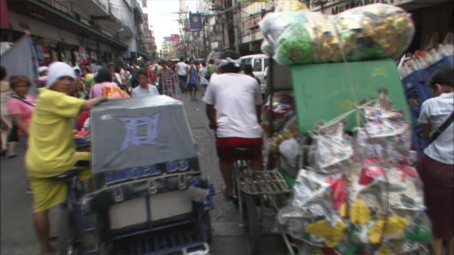Medium Shot POV -  View following a pedicab down city street lined with market stall and crowded with pedestrians / Manila Philippines