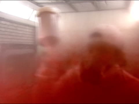 medium shot view from opposite side of glass as man spray paints car red in auto refinishing facility - spray painting stock videos & royalty-free footage