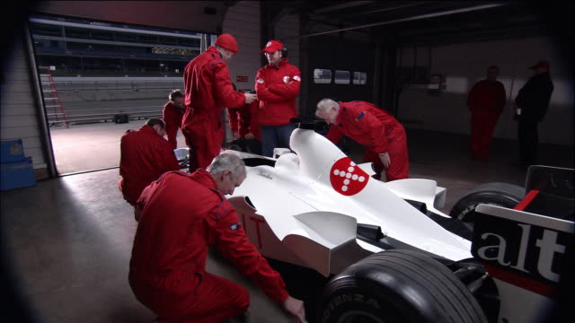 medium shot view of mechanics working on formula one race car in garage / zoom in crew member wiping down car - lenkrad stock-videos und b-roll-filmmaterial