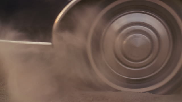 Medium shot view of rear wheel kicking up dust as car pulls away