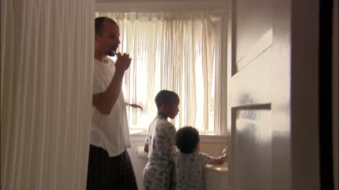 medium shot view through bathroom doorway of father and two young sons brushing teeth in morning - morning stock videos & royalty-free footage