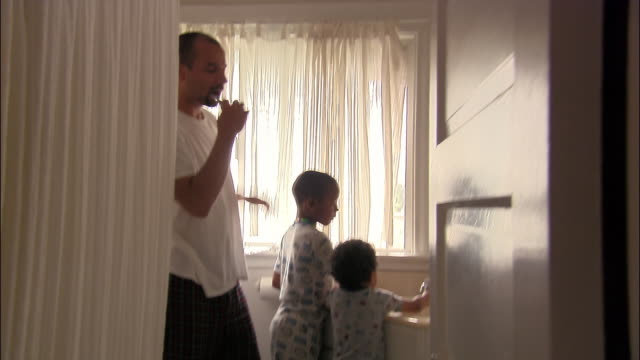 vídeos de stock, filmes e b-roll de medium shot view through bathroom doorway of father and two young sons brushing teeth in morning - escovar dentes