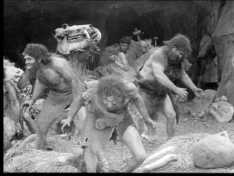 1914 B/W Medium shot Violent cavemen attacking boys and carrying cavewomen away