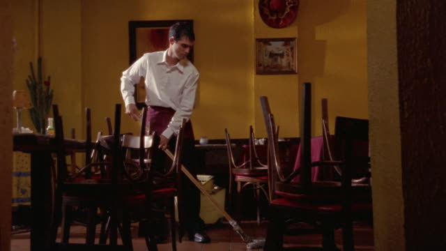 Medium shot waiter mopping floor of closed restaurant / chairs on top of tables / laughing and dancing