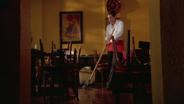 medium shot waiter mopping floor of closed restaurant / chairs on top of tables / laughing and dancing - caretaker stock videos & royalty-free footage