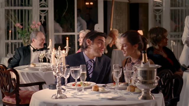 medium shot waiter serving young couple at formal restaurant / couple toasting each other / talking and kissing - luxus stock-videos und b-roll-filmmaterial