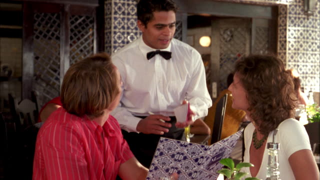 Medium shot waiter taking order from man and woman in restaurant