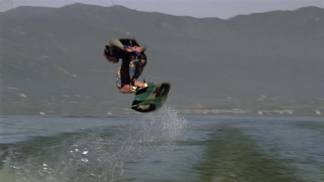 medium shot wakeboarder doing 360 turn / lake elsinore, california - ウェイクボーディング点の映像素材/bロール
