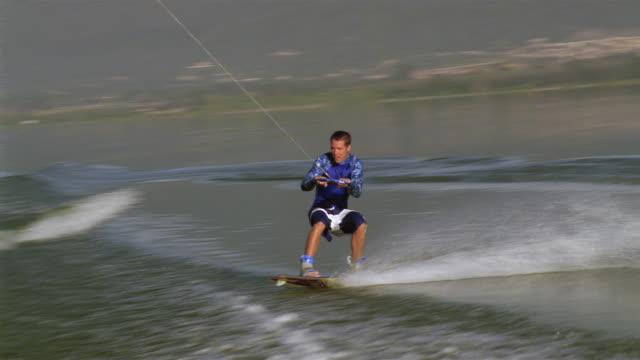 Medium shot wakeboarder flipping over / Lake Elsinore, California